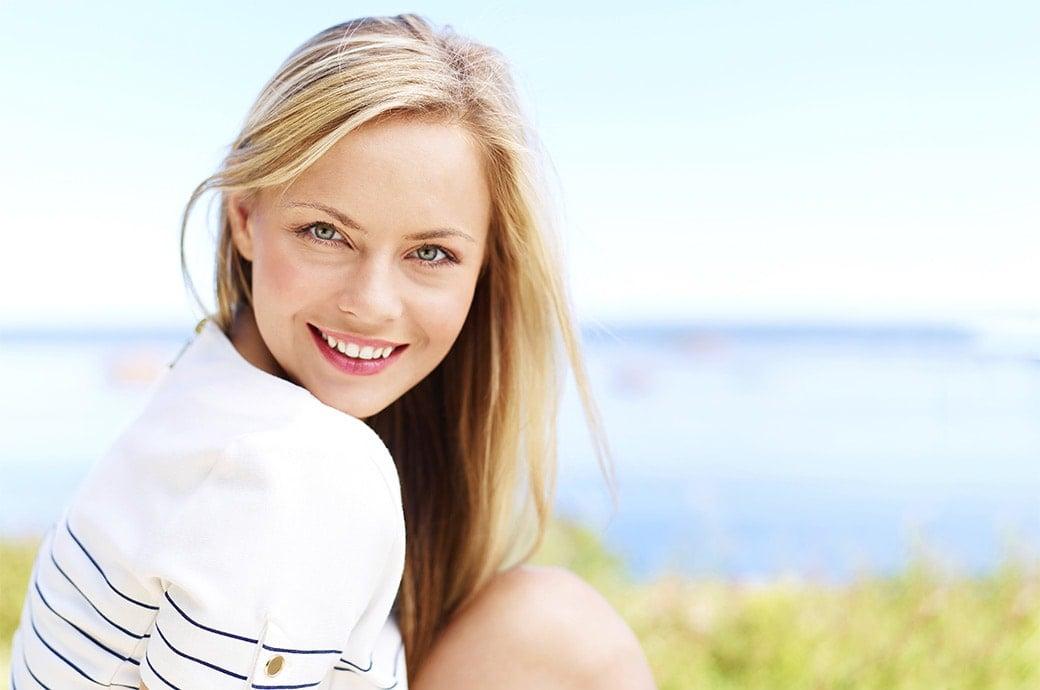 Le soleil brille… une femme souriante s'assoit sur l'herbe.