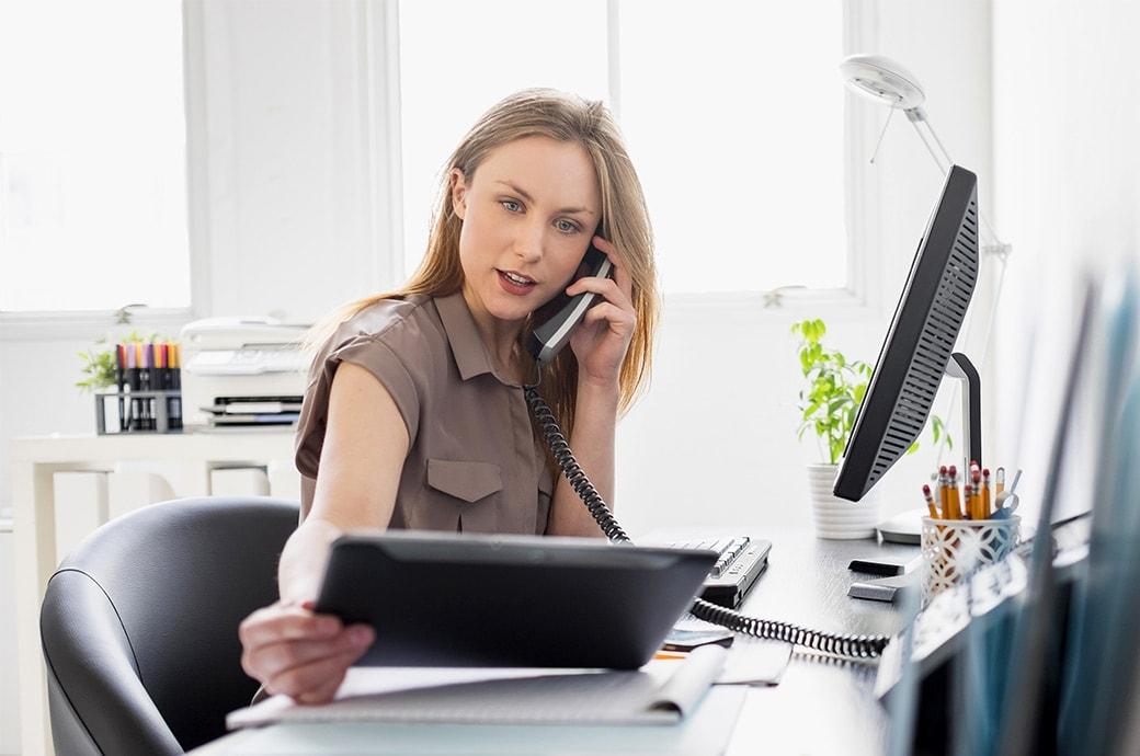 Une femme à son bureau de travail qui regarde une tablette et parle au téléphone.