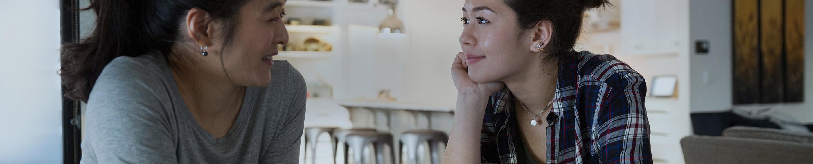 Une jeune femme qui parle à sa mère dans la cuisine