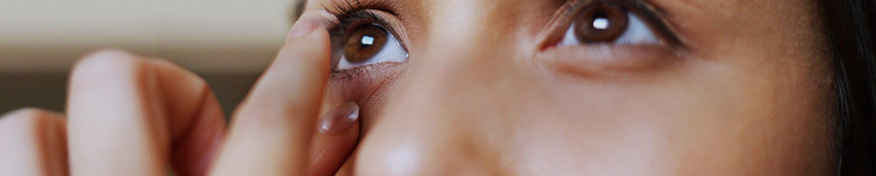Une vue rapprochée d'une jeune femme qui regarde dans un miroir pendant qu'elle insère ses lentilles dans les yeux