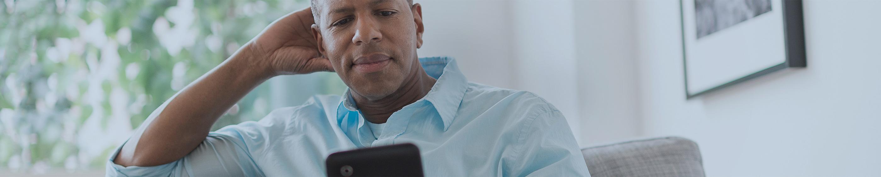 Un père de famille assis sur un canapé en train de lire sur sa tablette
