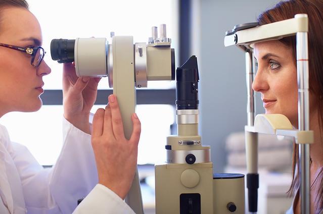 Une vue latérale d'un professionnel de la vue et d'une jeune femme qui regarde dans un rétinographe
