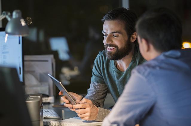 Deux hommes qui parlent tandis que l'un d'eux regarde une tablette