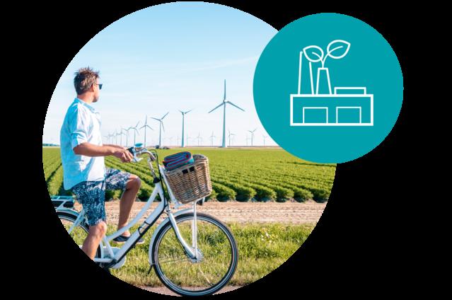 Un homme qui regarde les moulins à vent; il utilise de l'énergie propre réduisant ainsi son empreinte carbone.
