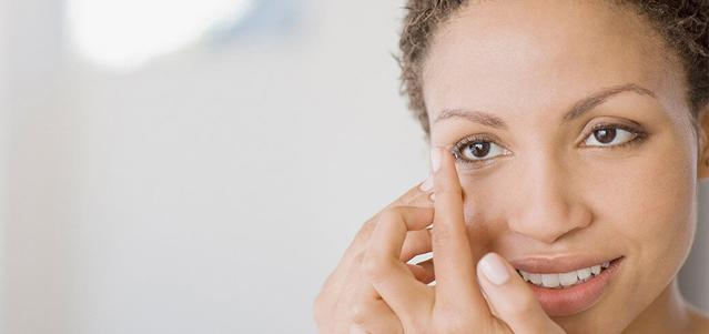 Une femme tenant une lentille sur son doigt qui s'apprête à l'insérer sur son œil
