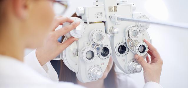 A young woman behind a phoropter as the doctor checks her eyes during an eye exam