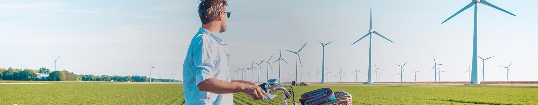 Un homme regarde les moulins à vent qui réduisent les émissons de gaz carbonique et l'empreinte carbone