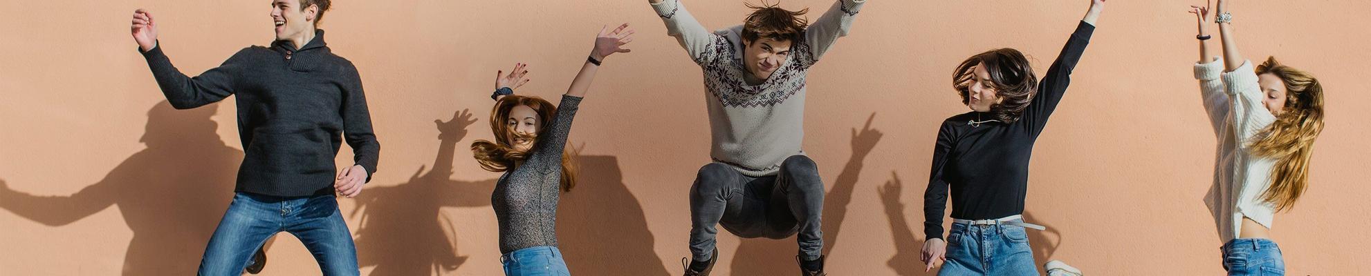 Un groupe d'amis qui sourient et sautent dans les airs avec les bras au-dessus de la tête