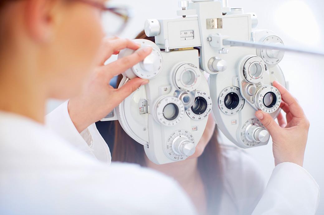 Une jeune femme derrière un réfracteur durant un examen de la vue effectué par un professionnel de la vue
