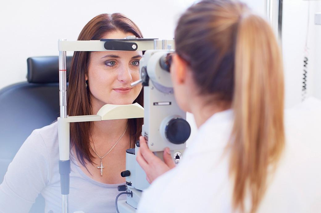 La caméra se pose sur une jeune femme qui regarde dans un rétinographe pendant que le professionnel de la vue regarde de l'autre côté de l'appareil