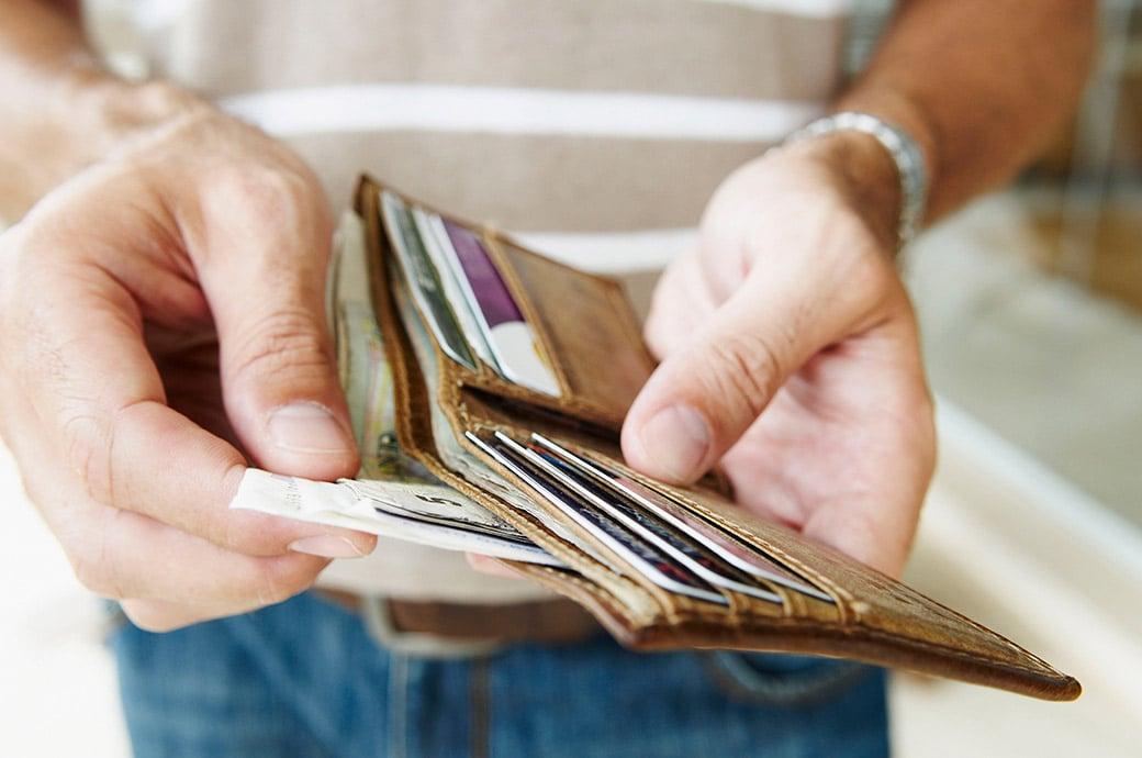 Une vue rapprochée de quelqu'un qui sort des billets de banque de son portefeuille