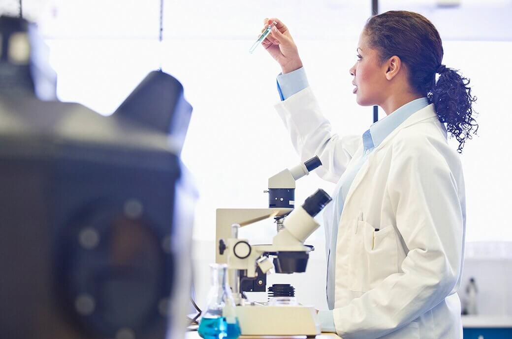 Un professionnel de la vue qui se tient devant un microscope dans un laboratoire et examine attentivement un tube à essai