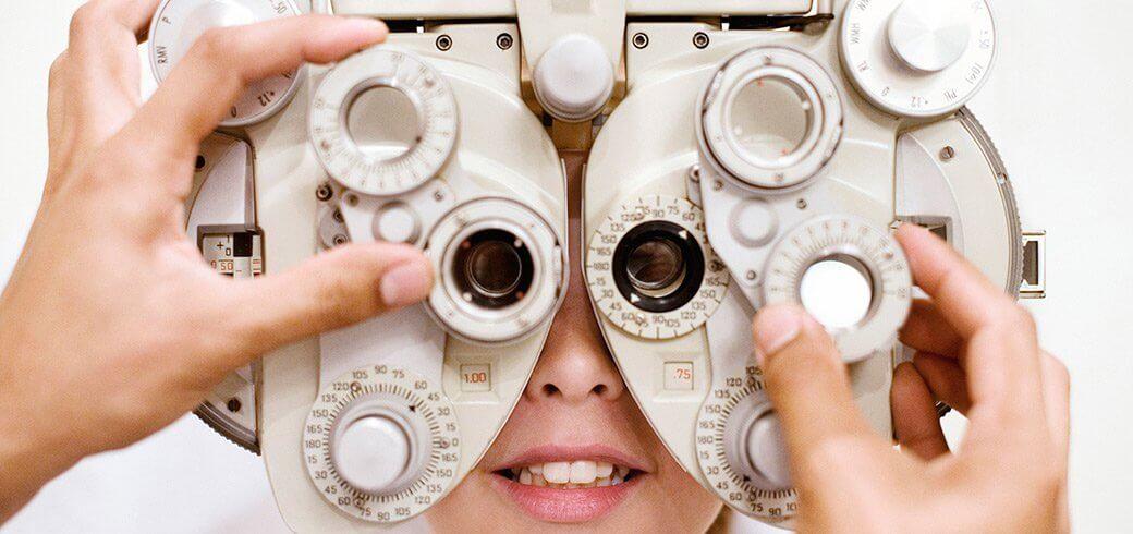 Un professionnel de la vue ajuste un réfracteur tandis qu'une jeune femme regarde dans les couronnes