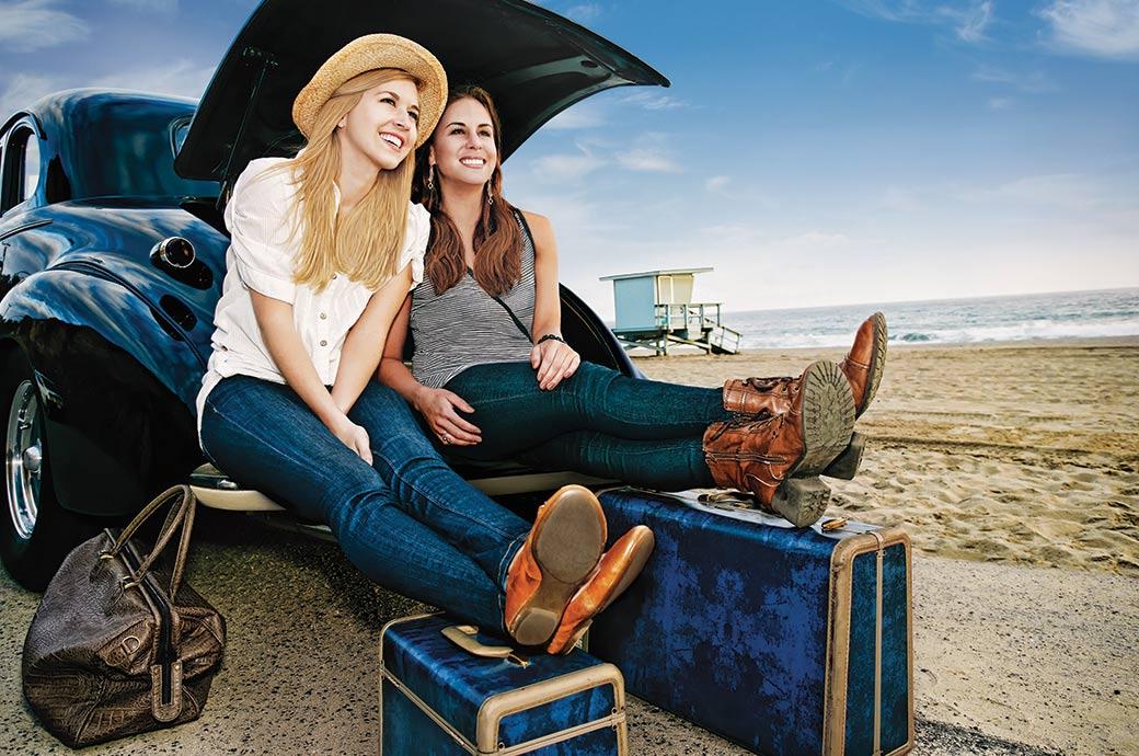 Deux jeunes femmes assisent dans le coffre d'une voiture stationnée près de la plage avec leurs valises, prêtes à partir en voyage